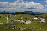 A landscape of Slovenian herders' holiday mountain huts in Velika Planina, on 26th June 2018, in Velika Planina, near Kamnik, Slovenia. Velika Planina is a mountain plateau in the Kamnik–Savinja Alps - a 5.8 square kilometres area 1,500 metres (4,900 feet) above sea level. Otherwise known as The Big Pasture Plateau, Velika Planina is a winter skiing destination and hiking route in summer. The herders' huts became popular in the early 1930s as holiday cabins (known as bajtarstvo) but these were were destroyed by the Germans during WW2 and rebuilt right afterwards by Vlasto Kopac in the summer of 1945.