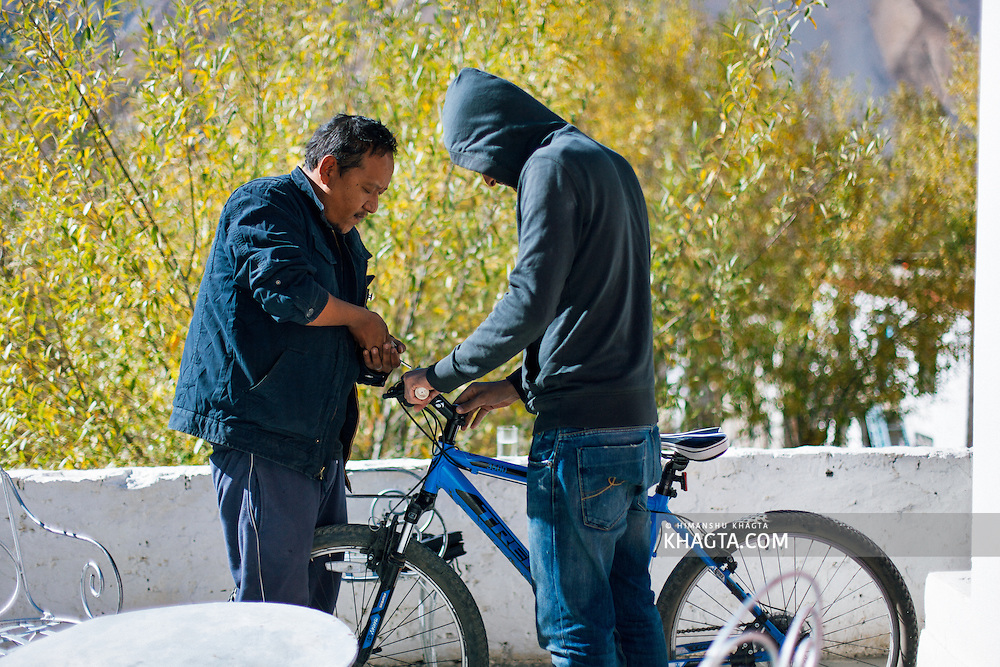 Tsering Bodh, fixing a mountain bike at Hotel Sakya Abode, Spiti, Himachal Pradesh, India