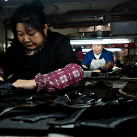 Chongqing, China - 31 December 2010:  a woman works on boots in a small manufacturing factory producing shoes. According to a report published by Bank of America Merrill Lynch's David Cui, titled 'Not So Trivial Facts', China has produced in 2010 a total of 12.6 billion pairs of shoes which means 9.4 pairs of shoes per person, compared with 1.3 pairs in the rest of the world (63.0 percent of global total).