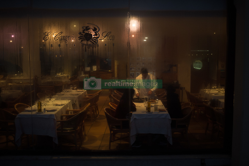 November 18, 2018 - Barcelona, Catalonia, Spain - In a restaurant of Barcelona a waiter serves paella to customers as rain falls outside. (Credit Image: © Jordi Boixareu/ZUMA Wire)