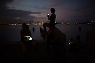 """People connect to the internet at a hotspot in Regla, Cuba, November 19, 2015. REUTERS/Alexandre Meneghini <br /> <br /> Resumen del ensayo: <br /> El acceso desde la casa al internet en Cuba sigue siendo restringido a la gran mayoría de la población. Su única posibilidad es acceder a un  """"hotspot"""", o zonas con internet wifi instalados por el gobierno y abiertos a todos los que compren una tarjeta para tener acceso al servicio. El paquete de fotos """"hotspots internet"""" tiene como ambición retratar el cotidiano de los cubano en estos hotspots."""