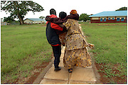 Bea Ahbeck/Fremont Argus 10/26/05<br /> <br /> People Having Aids' David Kiyuba and Susan's sister Mirabu Kasuswa carry Susan Izimba, 30, who is too weak to walk, to her hospital bed after she was admitted into Mulago Hospital in Kamuli, Uganda, Oct. 26, 2005. Susan was found to be anemic, but the hospital doesn't have any blood, and she needs money to be transferred to a different hospital to be treated for the tuberculosis and possibly get blood, if it's available.