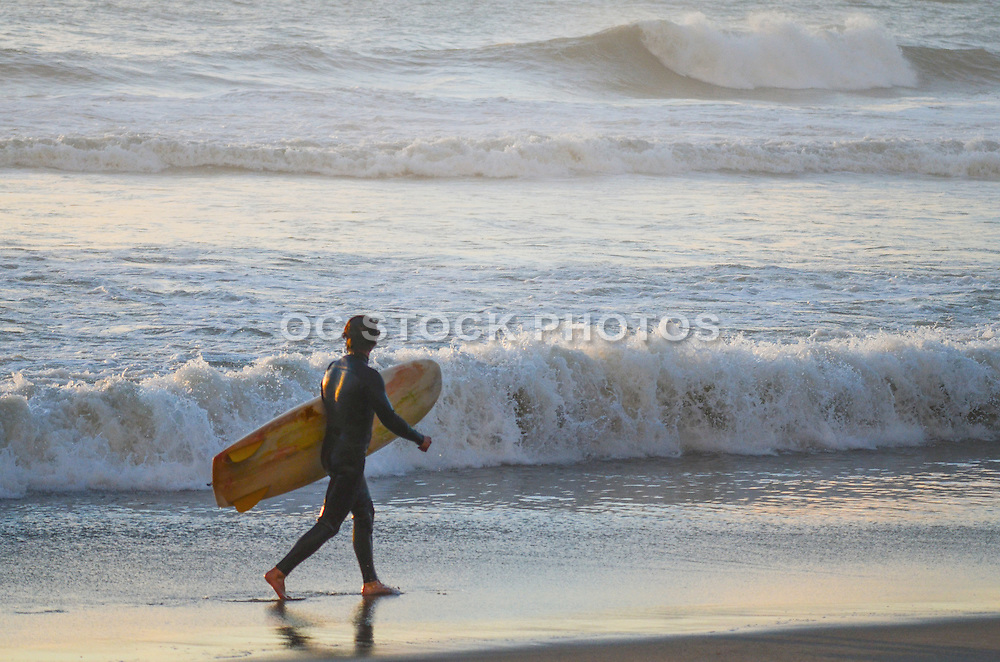 Male Walking with Surfboard on the Beach Looking at the Waves