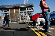 Passers-by are walking their dogs through the BedZED housing complex on Thursday, Sep. 6, 2007, in London, UK. BedZED or the Beddington Zero Energy Development, is an environmentally-friendly housing development near Wallington, England in the London Borough of Sutton. It was designed by the architect Bill Dunster who was looking for a more sustainable way of building housing in urban areas in partnership between the BioRegional Development Group and the Peabody Trust. There are 82 houses, 17 apartments and 1,405 square meters of work space were built between 2000. The project was shortlisted for the Stirling Prize in 2003. The project is designed to use only energy from renewable source generated on site. In addition to 777 square meters of solar panels, tree waste is used for heating and electricity. The houses face south to take advantage of solar gain, are triple glazed and have high thermal insulation while most rain water is collected and reused. Appliances are chosen to be water efficient and use recycled water wherever possible. Low impact building materials were selected from renewable or recycled sources and were all originating within a 35 mile radius of the site to minimize the energy required for transportation. Also, refuse collection facilities are designed to support recycling and the site encourage eco-friendly transport: electric and LPG cars have priority over petrol/diesel cars, and electricity is provided by parking spaces appositely built for charging electric cars.