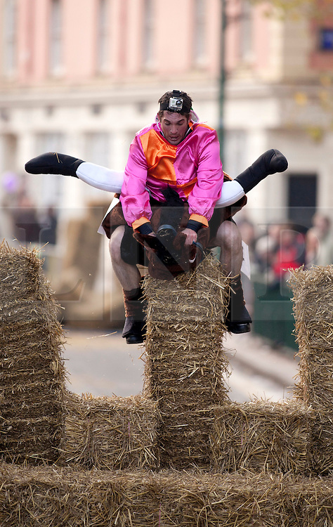 "© under licence to London News Pictures 28/11/2010 today picture. Birmingham`s wackiest Christmas event, the annual Pantominme Horse Grand National. The event that sees riders and horses race up and down Broad Street in the City Centre jumping over and even Through straw bales. Picture shows a sequence of rider Joel Hicks on his steed ""Viagra"" as he falls at a fence and completes the corse last..Picture credit: Dave Warren/London News Pictures..."