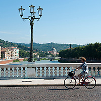 Woman riding a bike on a bridge over the river adige.Verona is a city in Veneton, Northern Italy home to approx. 265,000 inhabitants and one of the seven provincial capitals of the region. Verona has Roman origins and  derived importance from being at the intersection of many roads. It is world famous for the Arena and its Opera....***Agreed Fee's Apply To All Image Use***.Marco Secchi /Xianpix. tel +44 (0) 207 1939846. e-mail ms@msecchi.com .www.marcosecchi.com