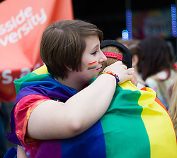 © Licensed to London News Pictures. <br /> 27/09/2014. <br /> <br /> Middlesbrough, United Kingdom<br /> <br /> A couple embrace during a parade through the centre of Middlesbrough. The parade was part of a Pride event that brings together many members of the Lesbian, Gay, Bisexual and Transgender community from the area.<br /> <br /> Photo credit : Ian Forsyth/LNP