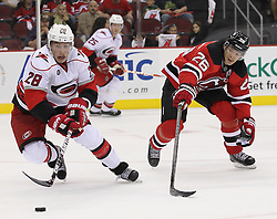 Oct 10; Newark, NJ, USA; Carolina Hurricanes defenseman Justin Faulk (28) skates with the puck while being defended by New Jersey Devils center Patrik Elias (26) during the second period at the Prudential Center.
