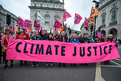"""© Licensed to London News Pictures. 22/02/2020. LONDON, UK.  Activists from Extinction Rebellion carrying a banner take part in march called """"Enough is enough, Together we march"""" from Russell Square to Parliament Square calling for governments to act on the negative effects of climate change.   Photo credit: Stephen Chung/LNP"""