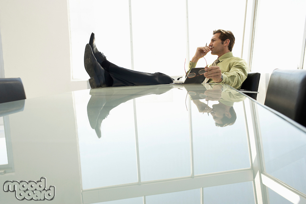 Businessman with feet up in conference room