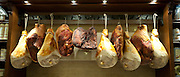 Shop window display of cured meats, hams, pork shoulders, at Dalmayr food shop and delicatessen in Munich, Bavaria, Germany