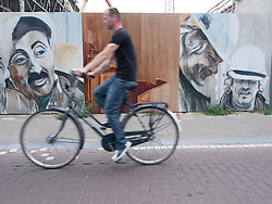 Cyclists riding past paintings on wall beside construction site for new Stedelijk Museum in Amsterdam The Netherlands