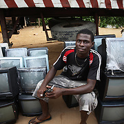 Electronic waste export to Nigeria...Alaba International Market, one of the largest markets for electronic goods in West Africa.  New and old - and a lot of non-working electronic goods such as TVs and computers come in to the market via Lagos harbour from the US, Western Europe and China...Container 4629416 from the UK is being emptied for its load, including the TV tracked by Greenpeace.  A laborer at the market with second hand televisions just in from Europe. . .The shipment - TV-set originally delivered to municipality-run collecting point in UK for discarded electronic products - was tracked and monitored by Greenpeace using a combination of GPS (Global Positioning System using satellites), GSM (positioning using data from mobile networks to triangulate approximate positions) and an onboard radiofrequency transmitter (used for making triangulations in combination with handheld directional receivers used by team on ground) is placed inside the TV-set.  The TV arrived in Lagos in container no 4629416.