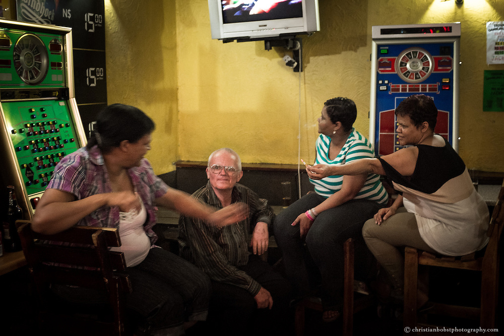 Father Hermann talks to some street walkers in a casino bar at Ausspannplatz in the city center of Windhoeck.