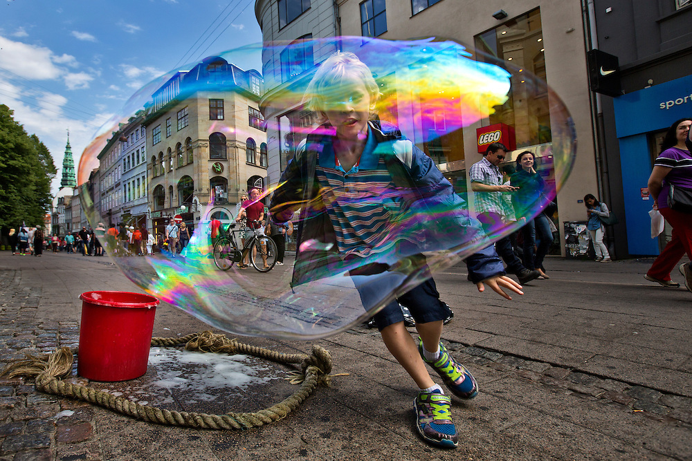 Copenhagen, Denmark.  On the city streets of Copenhagen, a young boy runs through the bubble of a bubble making street artist.