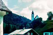 Austrian town and church with mountains in the background.