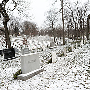 Headstones and the ground of Arlington National Cemetery is covered in a light blanket of snow after recent snowfall.