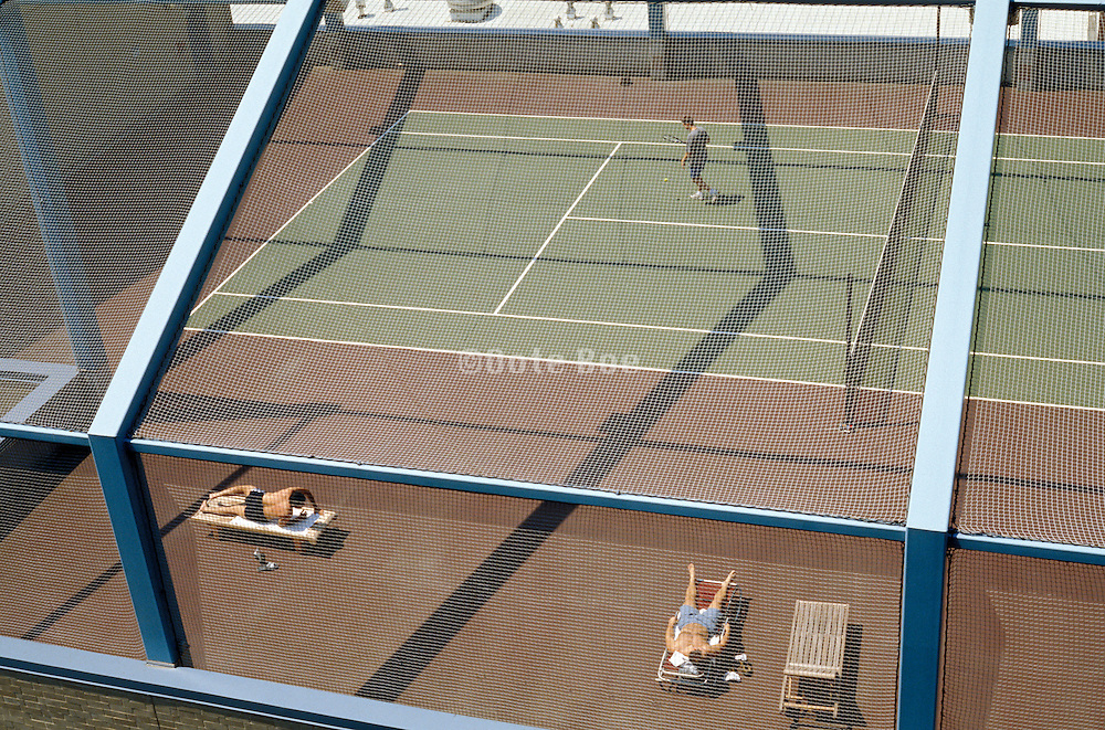 people sunbathing on a rooftop tennis court