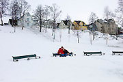 Young couple sitting on park bench in deep snow in Tromso, Norway