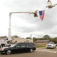The funeral procession for former Bruce Police Chief Stanley Evans makes its way under an American flag as they make their way ot the Zion Springs cemetery on Saturday.
