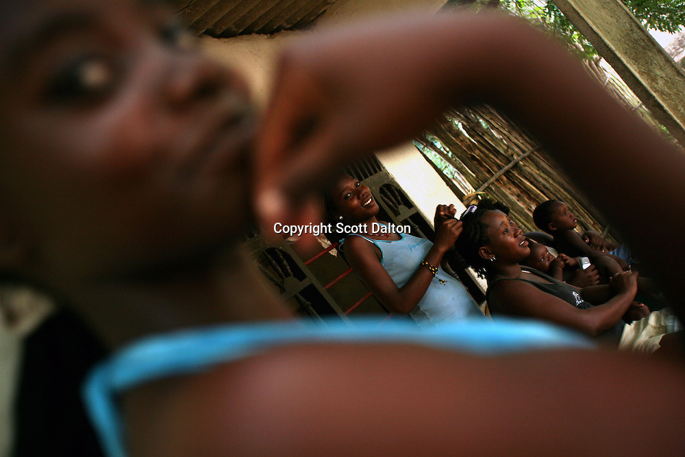 A woman has her hair braided in San Basilio de Palenque, in northern Colombia, about 50 kilometers outside of Cartagena, on Saturday, October 13, 2007. The town of San Basilio de Palenque, which was founded by runaway slaves at the beginning of the 17th century, is trying to maintain their native language known as Palenquero, a Spanish-based creole language whose unique grammar and African influences have astonished linguists. (Photo/Scott Dalton).