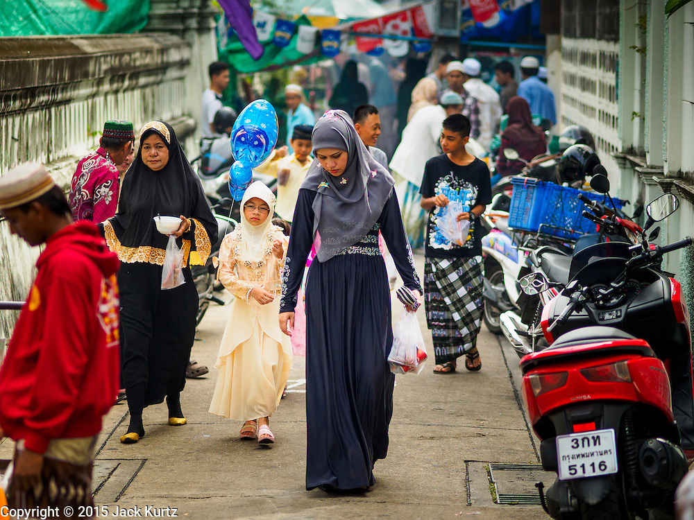 17 JULY 2015 - BANGKOK, THAILAND:     People walk in front of Ton Son Mosque in Bangkok after Eid services. Eid al-Fitr is also called Feast of Breaking the Fast, the Sugar Feast, Bayram (Bajram), the Sweet Festival or Hari Raya Puasa and the Lesser Eid. It is an important Muslim religious holiday that marks the end of Ramadan, the Islamic holy month of fasting. Muslims are not allowed to fast on Eid. The holiday celebrates the conclusion of the 29 or 30 days of dawn-to-sunset fasting Muslims do during the month of Ramadan. It's common to give children small gifts and toys, like helium balloons, for Eid. Islam is the second largest religion in Thailand. Government sources say about 5% of Thais are Muslim, many in the Muslim community say the number is closer to 10%.          PHOTO BY JACK KURTZ