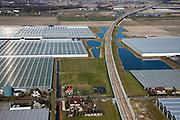 Nederland, Zuid-Holland, Bleiswijk, 20-03-2009; spoorbaan van de HSL verlaat het kassengebied Hoefweg-Zuid in de Overbuurtsche Polder en gaat met viaduct over de spoorlijn Zoetermeer - Goud (met gele intercity trein nog juist rechts in beeld). Tuinderswoningen in de voorgrond. The railway of the HST crosses the greenhouses area..Swart collectie, luchtfoto (toeslag); Swart Collection, aerial photo (additional fee required); .foto Siebe Swart / photo Siebe Swart