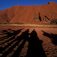 Australia, Northern Territory, Setting sun casts long shadows at base of Ayers Rock in Uluru National Park
