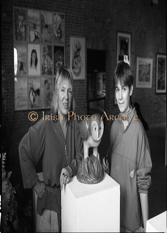 "Pauline Bewick Art Exhibition..1986..03.06.1986..06.03.1986..3rd June 1986..At the Guinness Hop Store,Dublin,artist Pauline Bewick is having an exhibition of her work.The exhibition called ""2 to 50 years""is a display of her work from age 2 to the present.the art work ranges from simple pencil sketches to more complex paintings and lino cuts...Photograph of the artist,Pauline Bewick, with her daughter Poppy.Poppy helped in the setting up of the exhibition with her mother. In the foreground is the work ""Chianti Owl""which forms part of exhibition."