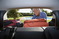 Senior man putting luggage into car boot