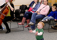 Jamison (right) and Debbie Simons, 3 of Centerville watch Lucy Clarke, 1, during holiday music from Centerville High School Orchestra members at the WashingtonCenterville Public Library in Centerville, Monday, December 5, 2011.