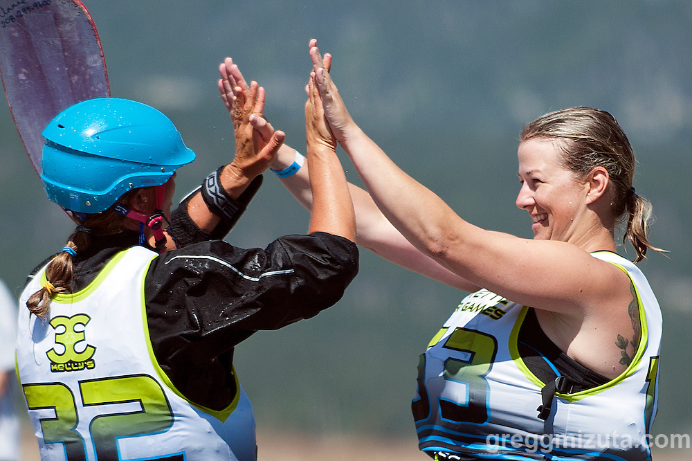 Annie Chamberlain and Laurie Rogers high five following Round 2 of the Payette River Games kayak xcross event at Kelly's Whitewater Park in Cascade, Idaho on June 21, 2014.