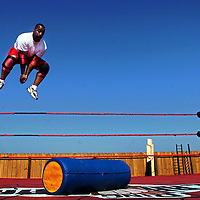 Eddie McKoy leaps from the ropes of the boxing ring in his backyard on Sunday Oct. 1, 2006. Eddie McKoy and Tony James, not pictured, spent a few hours practing their moves in the ring. Carolina Ring Wars is a wrestling organization with a cable access show and do charity events.