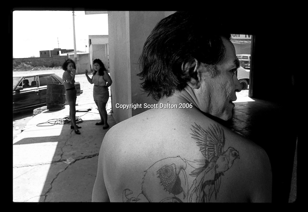 A man hangs out on the streets of Boystown, in Nuevo Laredo Mexico, just across the US-Mexico border from Laredo, Texas. Boystown is a walled community, only one way in or out, which is home to the cities prostitution and red light bars. Many of the prostitutes who work there are transsexuals and transvestites. The idea behind the walled community is to isolate the activities associated with red light districts. (Photo/Scott Dalton)