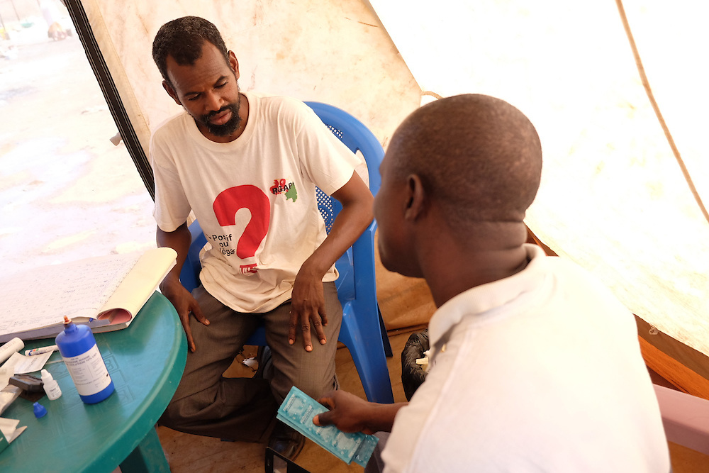 HIV activist Boubacar Alpha Diallo gives a man condoms during a HIV testing at the MSF mobile clinic in the neighbourhood of Tombolia, Conakry, Guinea on March 18, 2016. The man in is an imam from the local mosque and explains that he has been faithful to his wife since they have been married. He is relieved when his results show he is HIV negative. Bouboucar encourages the man to ask his wife to be tested also to be completely sure they are both HIV negative. MSF launched a HIV testing campaign in Conakry with the support of health authorities moving throughout several neighbourhoods throughout 2016.<br /> <br /> Despite countries in West and Central Africa having a relatively low HIV prevalence (