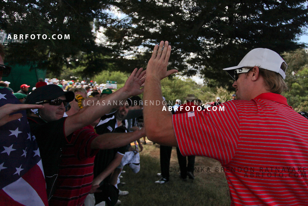 20 November 2011 : Hunter Mahan hi-fives American supporters during the fifth-round Sunday Final round single ball matches at the Presidents Cup at the Royal Melbourne Golf Club in Melbourne, Australia. .
