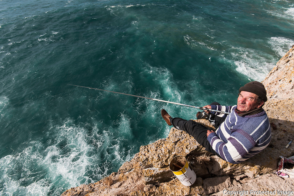 An old fearless fisherman, standing at the very edge of the Sagres Fortress cliff, waiting for the bite of a sea bream.