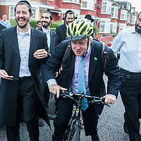London, UK - 7 August 2014: The Mayor Boris Johnson leaves with his bike after meeting Rabbi Oscher Schapiro and the Orthodox Jewish community in Stamford Hill, London