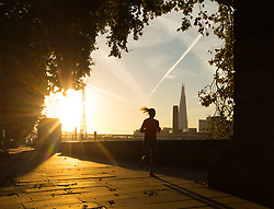 © Licensed to London News Pictures. 24/09/2018. London, UK. A woman runs along the Thames path shortly after sunrise on the River Thames during cold but sunny weather this morning.  Photo credit: Vickie Flores/LNP