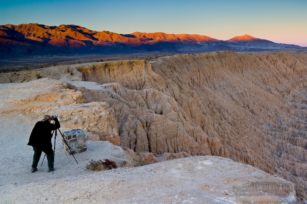 Photographer at sunset over eroded hills at the Borrego Badlands, from Fonts Point, Anza Borrego Desert State Park, San Diego County, California