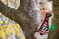 Thoughtful young woman in warm clothing standing near trees in park