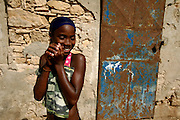 Shy girl still wet from swimming in Vila do Maio beach. The beach is located  just in front of the capital village and is the most accessible and, at the sime time,  most famous postcard image from Maio island. Fishing boats go out every day from the traditional pier.