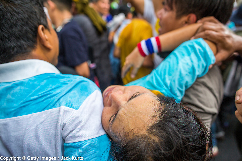 24 NOVEMBER 2012 - BANGKOK, THAILAND: Protesters help carry a woman overcome by tear gas to safety during a large anti government, pro-monarchy, protest  on November 24, 2012 in Bangkok, Thailand. The Siam Pitak group, which sponsored the protest, cited alleged government corruption and anti-monarchist elements within the ruling party as grounds for the protest. Police used tear gas and baton charges againt protesters.       PHOTO BY JACK KURTZ