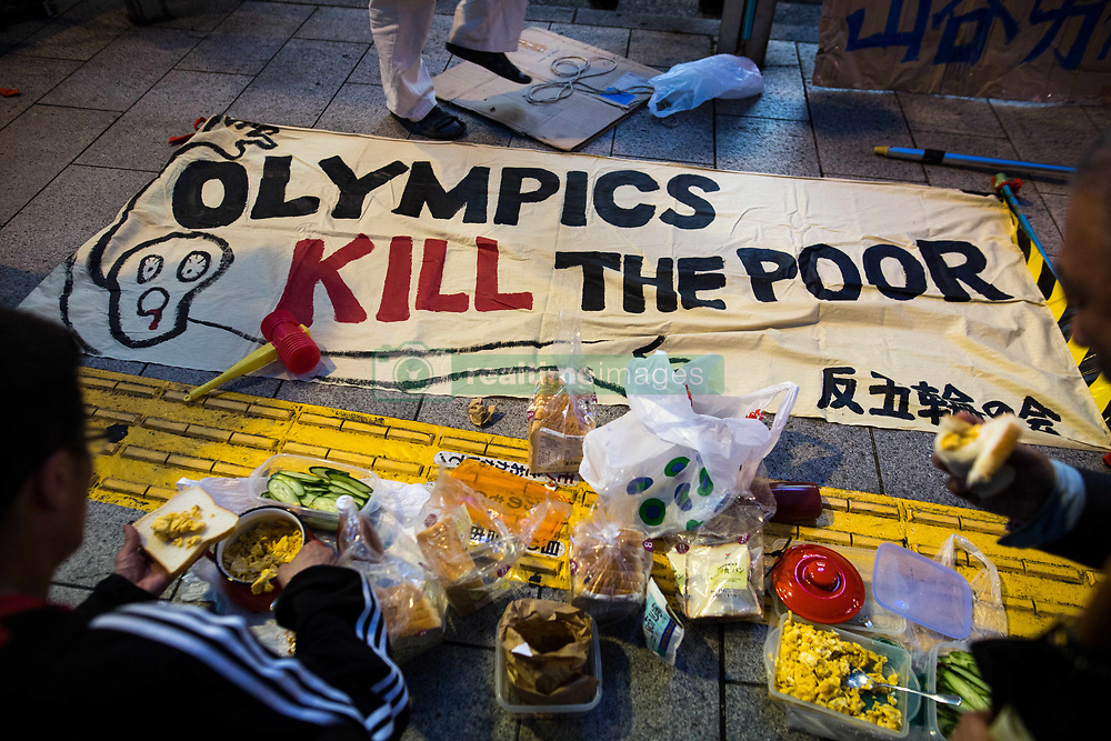 """June 30, 2017 - Shinjuku, Tokyo, Japan - Anti-Olympic protesters were seen eating with a signs on the ground that reads ''Olympics Kill the Poor"""" during a protest against hosting the Tokyo Olympic Games 2020 on Friday, June 30, 2017, downtown, Shinjuku, Japan. The protesters asked the Japanese government to use the Olympics funds for social spending and Olympic money would be better spent alleviating poverty. (Credit Image: © Richard Atrero De Guzman/NurPhoto via ZUMA Press)"""