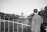 A visitor pauses on the Halfpenny Bridge to view the Liffey, the Quays and in the background rising starkly to it's 17th storey is the new skyscraper Liberty Hall..26.09.1963