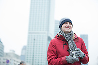 Happy man in warm clothing holding disposable cup outdoors