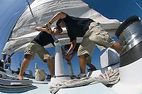 Sailors operating windlass on yacht low angle view