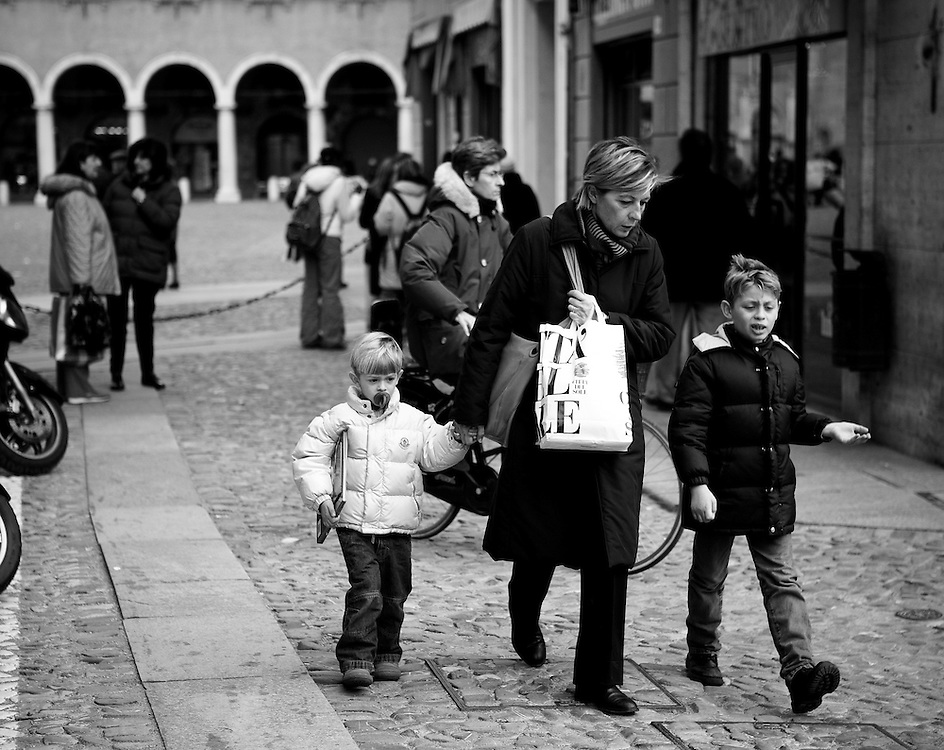 A mother and two children walking along a street in Modena, Italy.