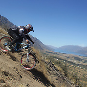 Caelab Drummond from Nelson in action during the New Zealand South Island Downhill Cup Mountain Bike series held on The Remarkables face with a stunning backdrop of the Wakatipu Basin. 150 riders took part in the two day event. Queenstown, Otago, New Zealand. 9th January 2012. Photo Tim Clayton