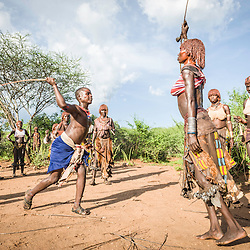 Before the bull jumping ceremony, the Maza whip the Hamer women who will defy them and show no fear or signs of pain . Hamer tribe, Omo valley, Ethiopia